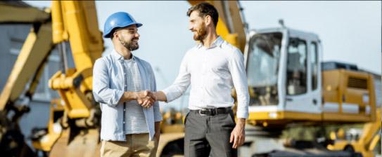 Dwaj mężczyźni na placu budowy wyrażający współpracę