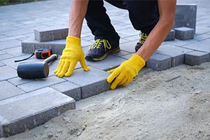 Pracownik w żółtych rękawiczkach układa kostkę brukową