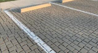 Miejsce parkingowe z kostki brukowej z namalowanymi pasami odstępu