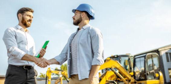Dwaj mężczyźni na placu budowy podający sobie ręce