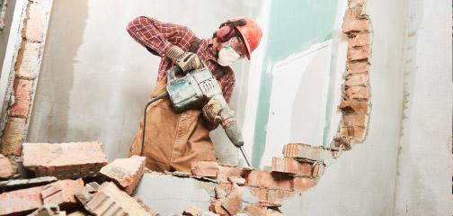 Robotnik podczas wyburzania ściany