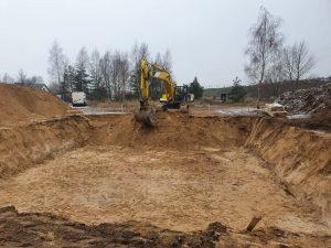 Koparka wykonująca przygotowanie działki pod budowę domu w ciągu dnia